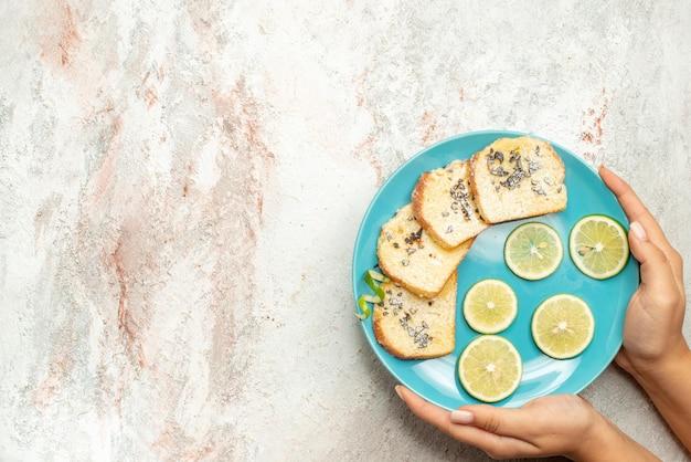 Draufsichtbrot und zitronenplatte mit geschnittenen zitrusfrüchten und weißbrot in der hand