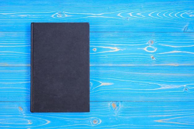 Draufsichtbuch und neuer moderner rosa musikkopfhörer auf blauer hölzerner planke