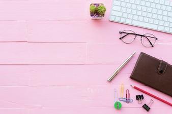 DraufsichtBürotisch mit Arbeitsplatz auf rosa hölzernem Hintergrund.