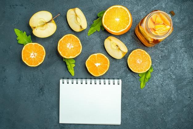 Draufsichtcocktail geschnittene orangen und äpfel auf dunklem, isoliertem hintergrund