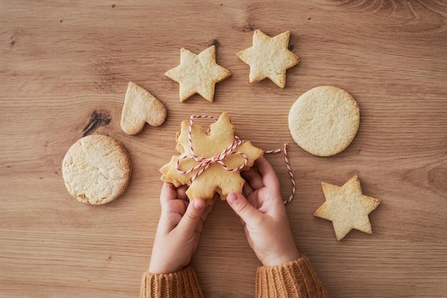 Draufsichtdetail von keksen, die von den händen des kindes gehalten werden