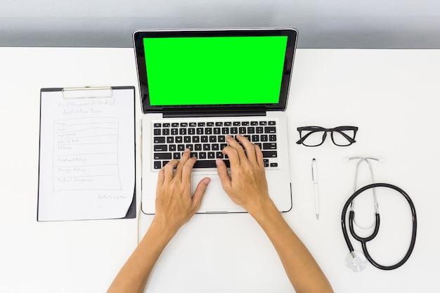 Draufsichtdoktor, der stark am schreibtisch mit laptop-ausrüstung des grünen schirmes arbeitet