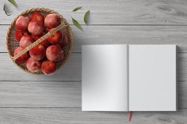 Draufsichtebenenlage-szene eines leeren rezeptnotizbuches und der äpfel des gesunden lebensmittels in einem handgemachten korb
