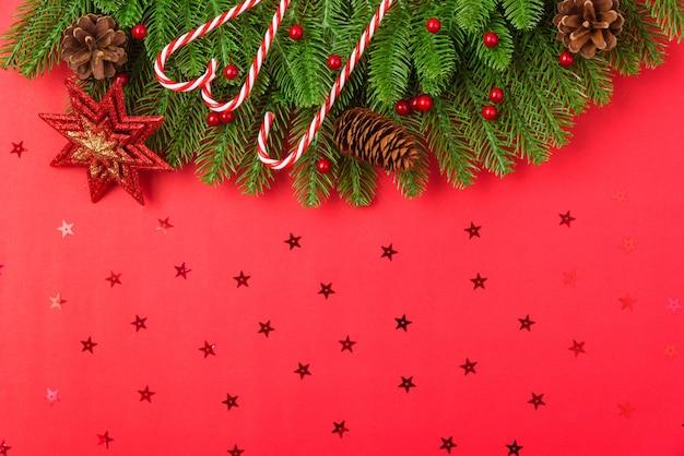 Draufsichtebenenlage-tannenbaumaste des guten rutsch ins neue jahr oder des weihnachtstages und verzierungsdekoration auf rot