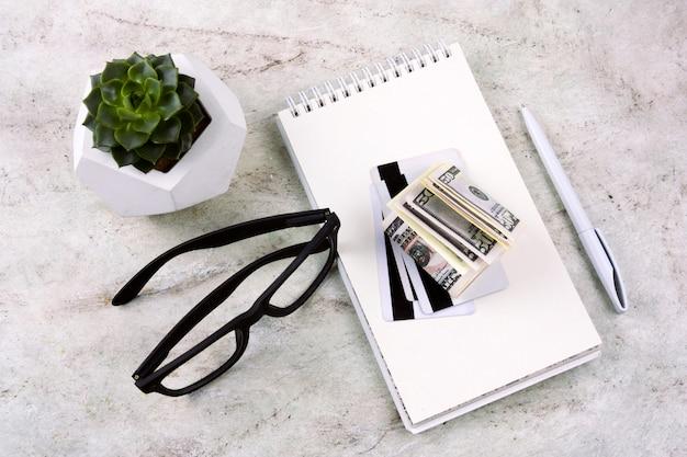 Draufsichtebenenlagenotizbuch, stift, geld, kreditkarten, gläser und succulent auf einer marmortabelle