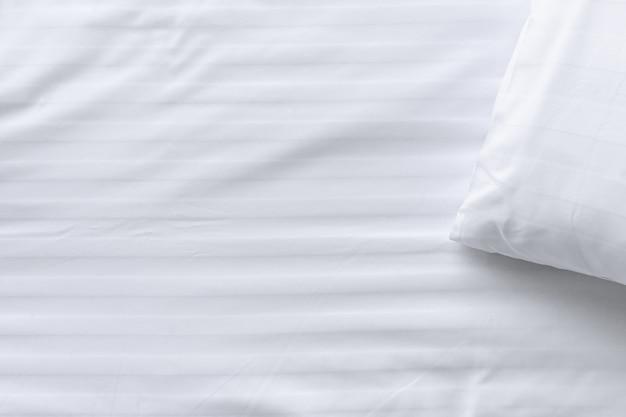Draufsichtecke des weißen kissens auf weißem sauberem bettabschluß oben, kopienraum