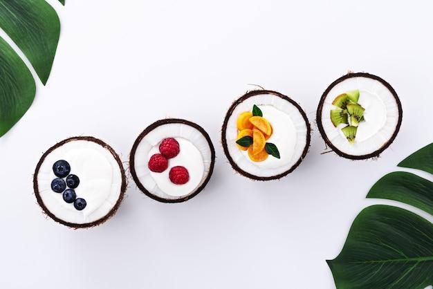Draufsichteis mit fruchtfüllern, joghurt in kokosnussschalen auf weißem hintergrund, trendiges dessertkonzept