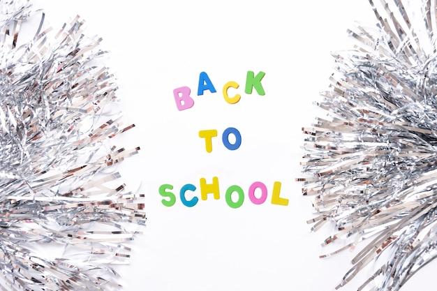 Draufsichtfahne von cheerleading silbernen pomponsfolienlamettastreifen und -buchstaben zurück zu der schule lokalisiert auf weißem hintergrund.