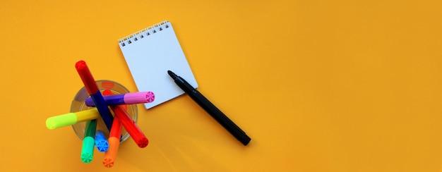 Draufsichtfahne von filzstiften und von leerem notizblock auf gelb
