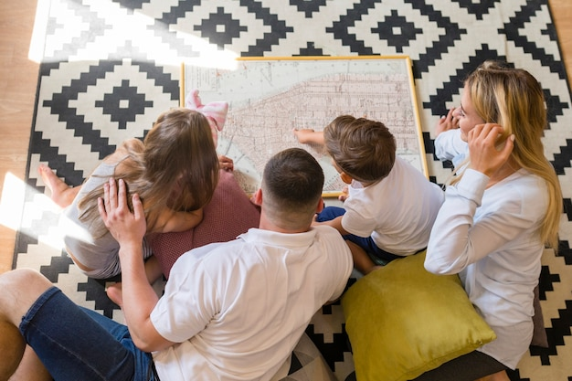 Draufsichtfamilie, die zuhause eine blaupause betrachtet