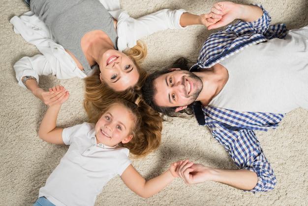 Draufsichtfamilienporträt, das auf teppich legt