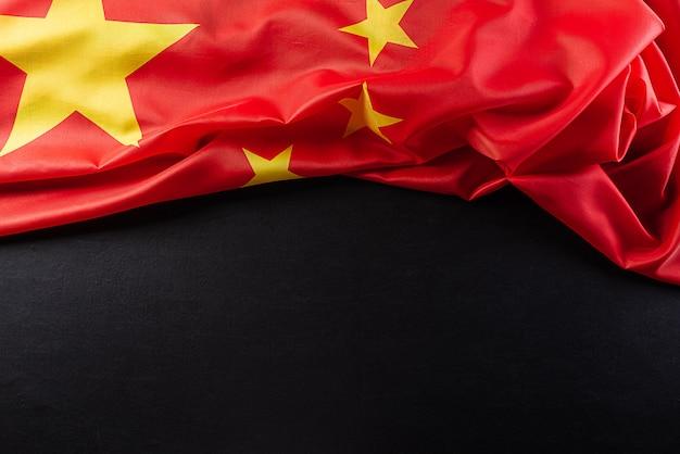 Draufsichtflagge der volksrepublik china auf schwarzer wand.
