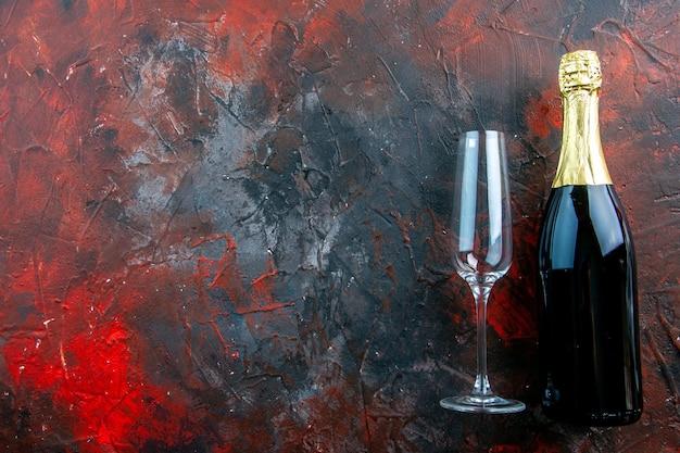 Draufsichtflasche champagner mit glas auf dem dunklen alkoholfarbfotogetränk