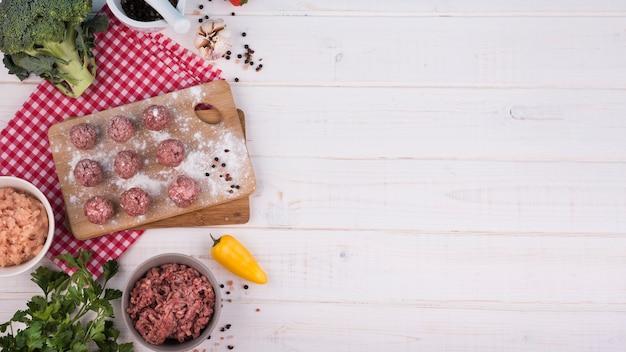 Draufsichtfleischklöschen auf hölzernem brett und hackfleisch mit kopienraum