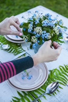 Draufsichtflorist macht einen blumenstrauß von vergissmeinnichtblumen und von farnblättern.