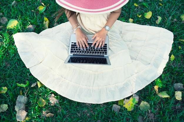 Draufsichtfoto der jungen frau, die laptop auf grünem garten des glases n verwendet.