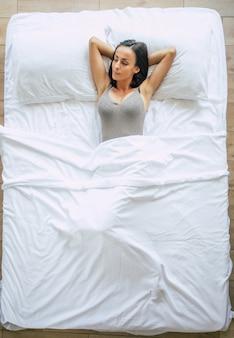 Draufsichtfoto der schönen jungen brünetten frau in einem großen weißen bett in ihrem schlafzimmer, während sie schläft. gute träume