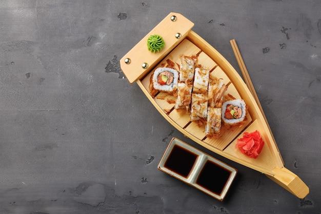 Draufsichtfoto der sushirolle mit thunfischspänen, die auf teller serviert werden