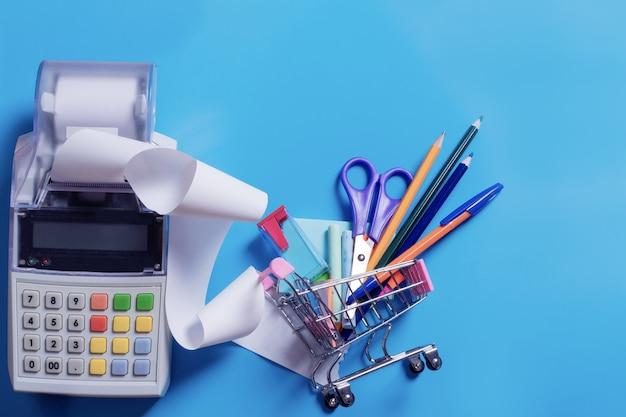 Draufsichtfoto des einkaufswagens mit buntem briefpapier und registrierkasse mit quittungsband einzeln auf blauem hintergrund. zurück zum schulkonzept