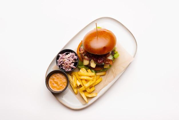 Draufsichtfoto einer platte mit burger und pommes auf weißem hintergrund.