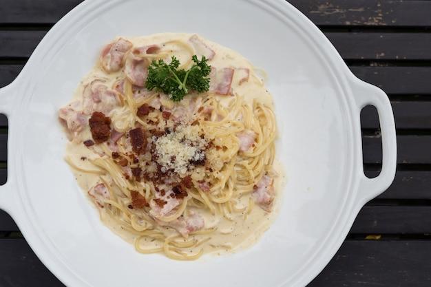 Draufsichtfoto von spaghetti carbonara-nudeln mit speck, käse und weißer soße auf holztisch. italienisches berühmtes essen mit kopienraum für text.