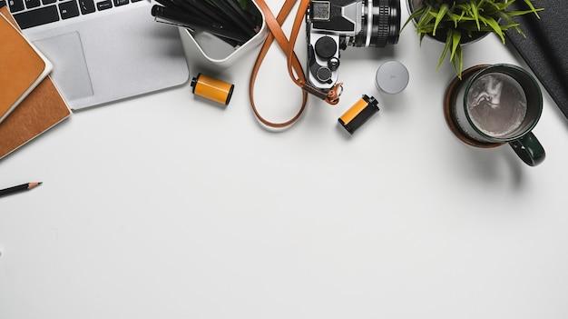 Draufsichtfotografarbeitsplatz mit laptop- und kamerazubehör auf weißer tablette mit kopienraum.
