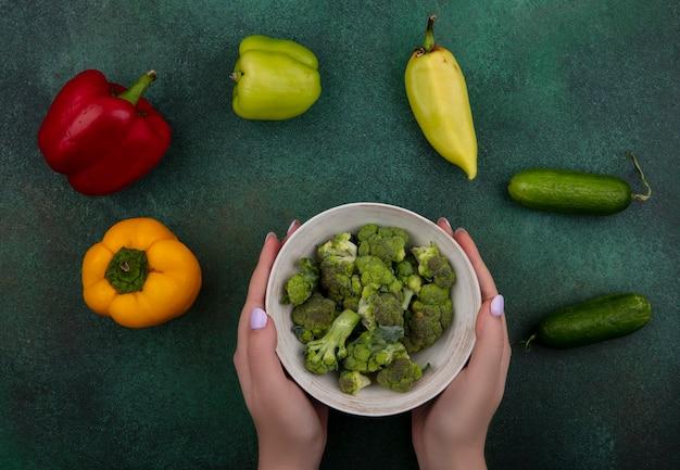 Draufsichtfrau, die brokkoli in der schüssel mit gurken und paprika auf grünem hintergrund hält