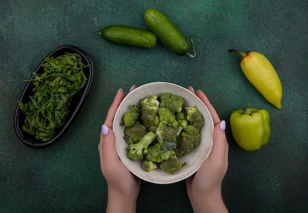 Draufsichtfrau, die brokkoli in einer schüssel mit gurkenkräutern und paprika auf einem grünen hintergrund hält