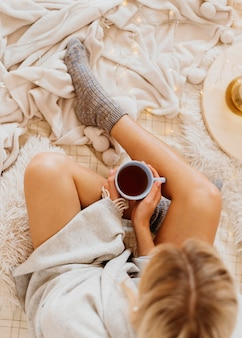 Draufsichtfrau, die eine tasse tee hält, während die winterferien genießt