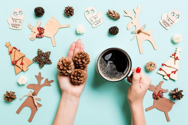 Draufsichtfrau, die einen schalenkaffee und kiefernkegel in ihren händen auf blau hält. weihnachtsdekorationen. zeit