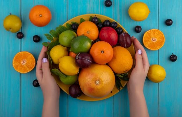 Draufsichtfrau, die einen teller mit gemischten früchten orangen kirschpflaumen grapefruit zitronen limetten und pflaumen auf einem türkisfarbenen hintergrund hält