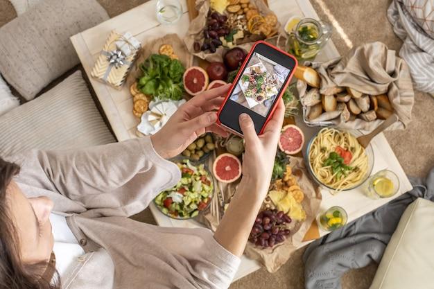 Draufsichtfrau, die esstisch mit dem servieren von leckerem essen und trinken fotografiert, verwendet smartphone