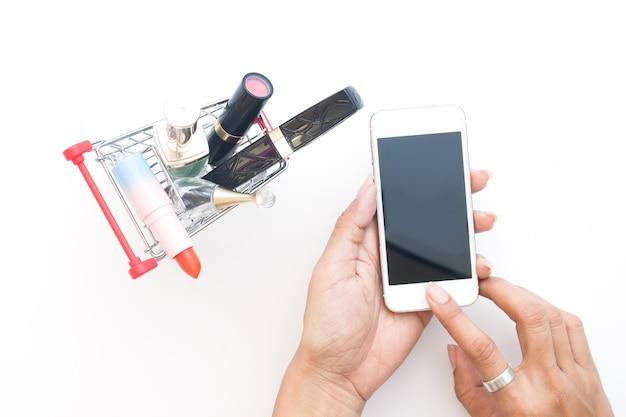 Draufsichtfrau, die handy mit kosmetik im einkaufswagen verwendet