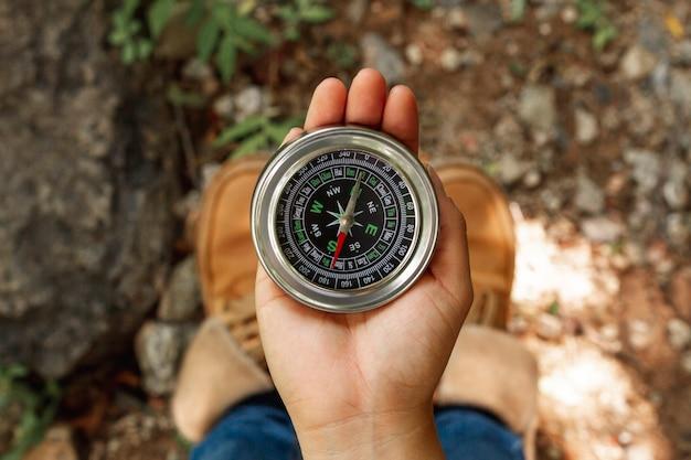 Draufsichtfrau, die kompass für richtungen verwendet