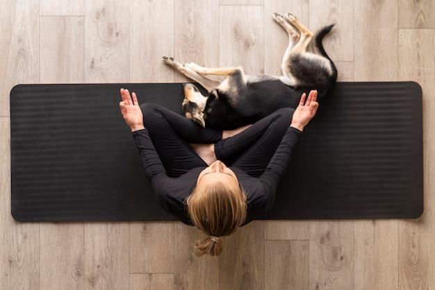 Draufsichtfrau, die mit hund meditiert