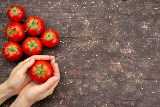 Draufsichtfrau, die reife tomaten und frisches gemüse auf braun hält