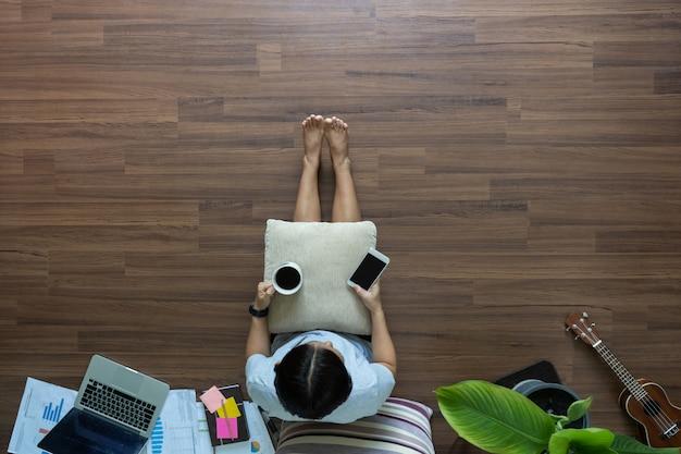 Draufsichtfrau, die unter verwendung des smartphones und des kaffeetrinkens auf holzboden entspannt