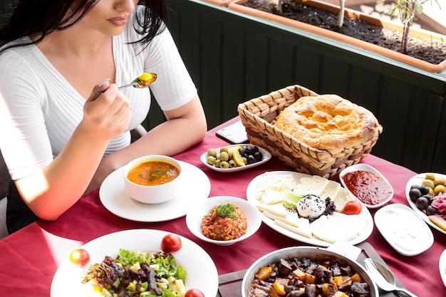Draufsichtfrau isst hühnersuppe mit salaten und käse