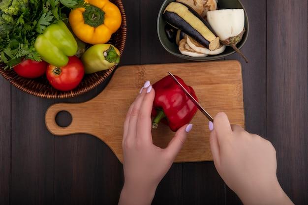 Draufsichtfrau schneidet rote paprika auf einem schneidebrett mit petersilie und tomaten in einem korb und auberginen auf einem hölzernen hintergrund