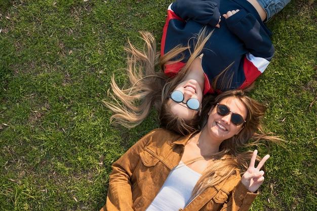 Draufsichtfrauen, die auf gras sitzen