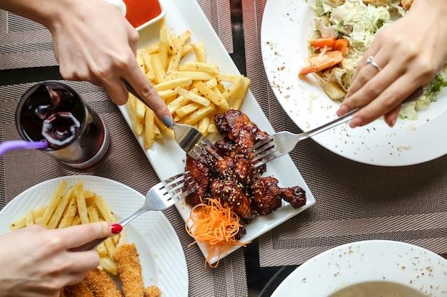Draufsichtfrauen, die grillhähnchenflügel mit pommes und salat mit saft auf dem tisch essen