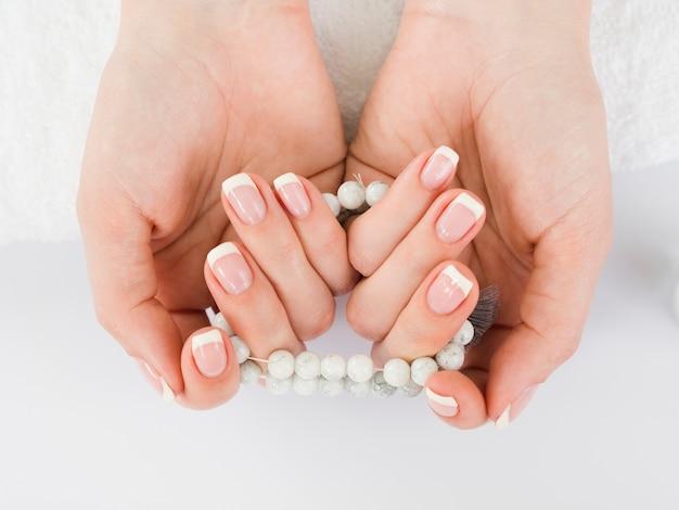 Draufsichtfrauenhände, die perlen halten