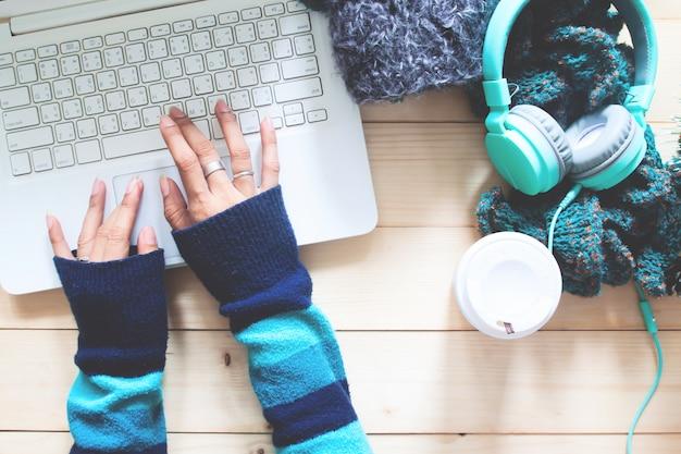 Draufsichtfrauenhände mit strickjacke unter verwendung des laptops auf arbeitsplatzschreibtisch. herbst oder winter