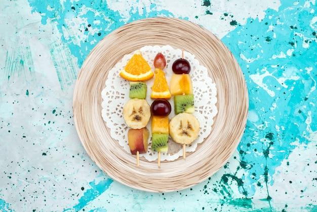 Draufsichtfrüchte auf stöcken innerhalb platte auf dem blauen hintergrundfrucht-sommerfarbfoto