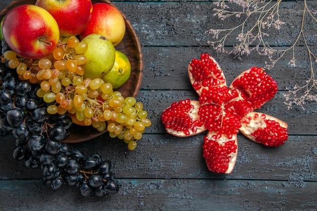 Draufsichtfrüchte in schüsselschale mit weißen und schwarzen trauben limetten äpfel birnen neben pilliertem granatapfel und ästen auf grauer oberfläche