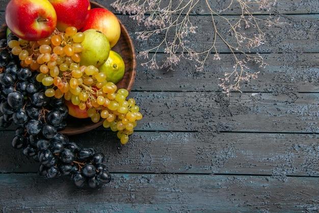 Draufsichtfrüchte in schüsselschale mit weißen und schwarzen trauben limetten birnen äpfel neben ästen auf dunkler oberfläche
