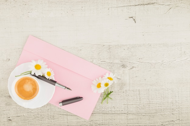 Draufsichtgänseblümchen und -kaffee auf hölzernem hintergrund