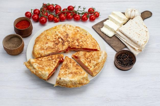 Draufsichtgebäck mit gemüse zusammen mit weißem käse und frischen tomaten auf dem weißen schreibtischessenmahlzeit-mittagsfoto