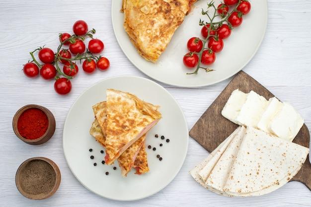 Draufsichtgebäck mit gemüse zusammen mit weißkäse-saisonzeichen und frischen tomaten auf dem weißen hintergrundnahrungsmittelmahlzeit-mittagsfoto