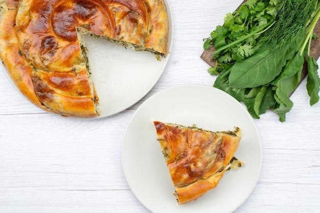 Draufsichtgebäck mit grün gekocht zusammen mit frischem grün auf dem weißen schreibtisch essen mahlzeit abendessen foto